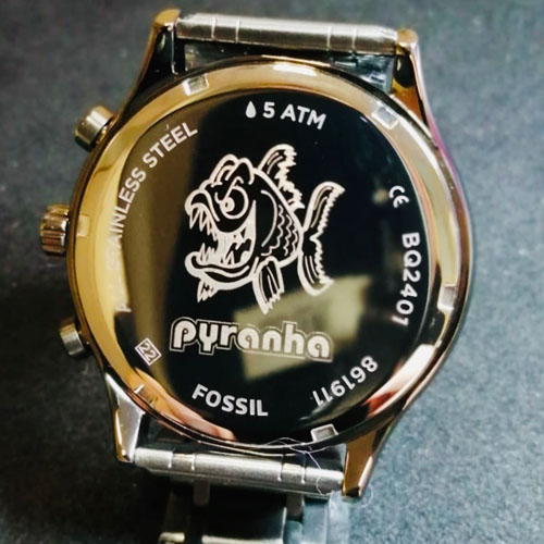 Machine engraved logo on Fossil watch case