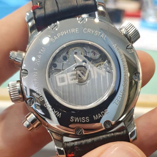 Machine engraved in reverse on the inside of a glass watch back