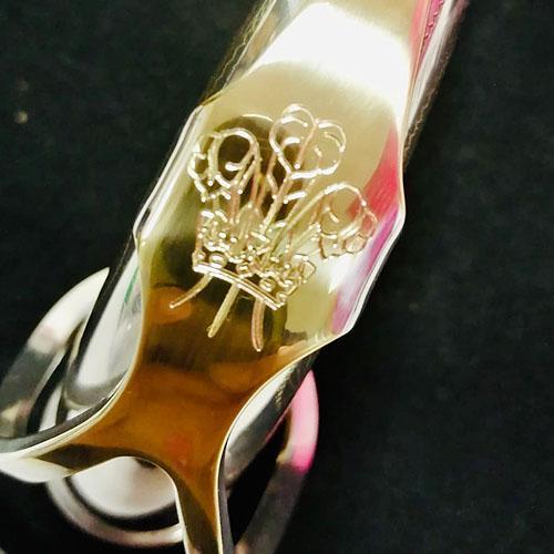 Machine engraved fleur-de-lis on a saxophone